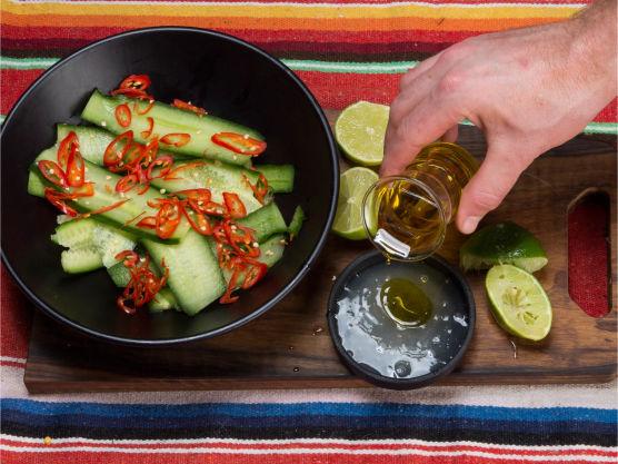 Bland sukker og limejuice, bland i olivenoljen. Kutt chilien i tynne skiver og tilsett. Hell dressingen over agurkstrimlene og smak til med salt og pepper. Den friske agurken mildner den sterke chilien.