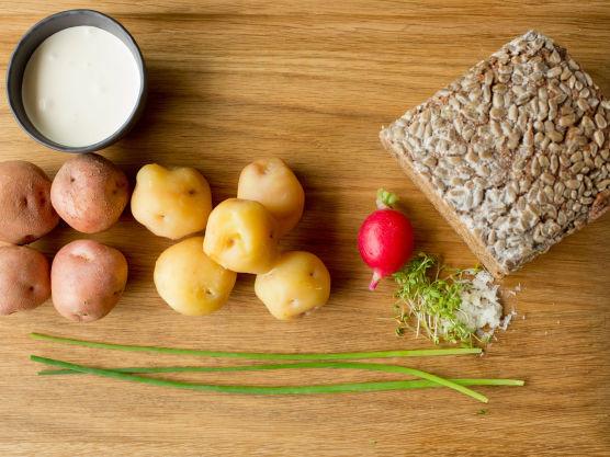 Skjær poteter, brød og reddik i skiver. Riv pepperrot. Smør brødskiven med smør hvis ønskelig. Legg på poteter og noen reddikskiver. Topp med rømme, revet pepperrot, hakket gressløk, salt og pepper.