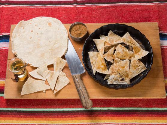 Kutt hver tortilla i ca. 12 trekanter og tørk disse, gjerne over natten på benken eller litt i ovnen. Friter trekantene i matolje på 180 grader og legg dem over på litt papir. Ha på adobo tacokrydder (kjøpt eller se egen oppskrift) rett etter fritering. Hvis du skal bake dem sprø i ovnen, har du på krydder og litt olje før bakingen.