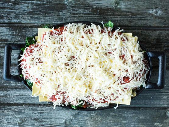 Legg på den siste pastaplaten og fordel resten av cottage cheese-blandingen og tomatsausen på toppen. Dryss over revet ost.