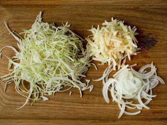 Snitt kålen i tynne strimler, ikke bruk den tykke midtstilken. Skjær løken i tynne skiver, skrell eplene og del dem i båter. Legg kål, løk, epler, karve og salt lagvis i en passende kjele. Hell over væske og la kålen surre/småkoke under lokk i ca. 45 minutter. Rør om av og til.