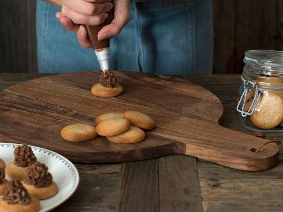 Bruk en bred smørekniv eller sprøytepose, og smør sjokoladekremen på mandelmakronene slik at de får høy, rund fasong. Sett kakene på et brett og legg i fryseren minimum 25 min, til sjokoladekremen på kakene har stivnet.