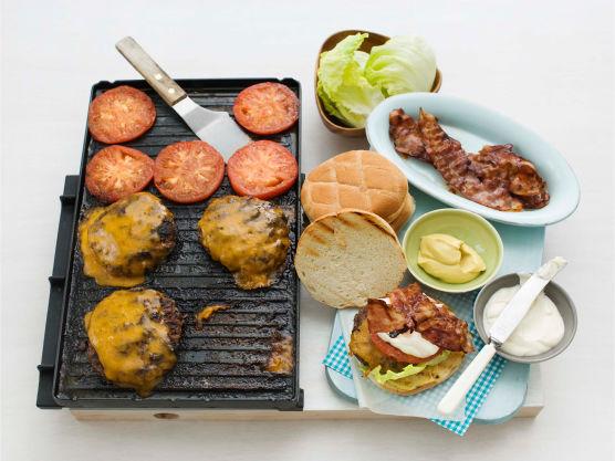 Varm hamburgerbrødene på grillen eller i ovnen på 200C. Ha på sennep og salat på brødbunnen, legg på burgere, grillet tomat og bacon, og topp med aioli og brød.