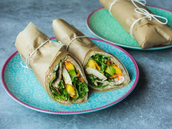 Smør wrapen med et tynt lag dressing. Legg på salatblader, kylling, avokado, mango og gulrot. Rull wrapen stramt sammen og pakk den inn i matpapir eller folie.