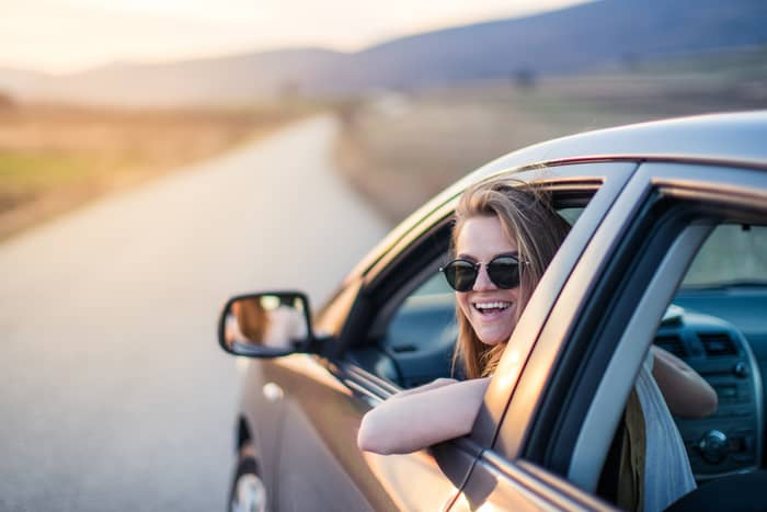 Ung jente som sitter i bil med solbriller og kjører på vei i solnedgang