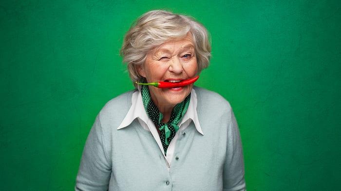 Gammel sprek dame som blunker til kamera med en chilli i munnen