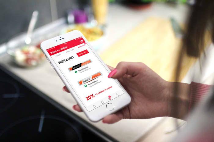 Hånd som holder i en telefon med bilde av kuponger fra MENY
