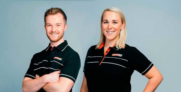 Mann og dame i SPAR-uniform som smiler mot kamera