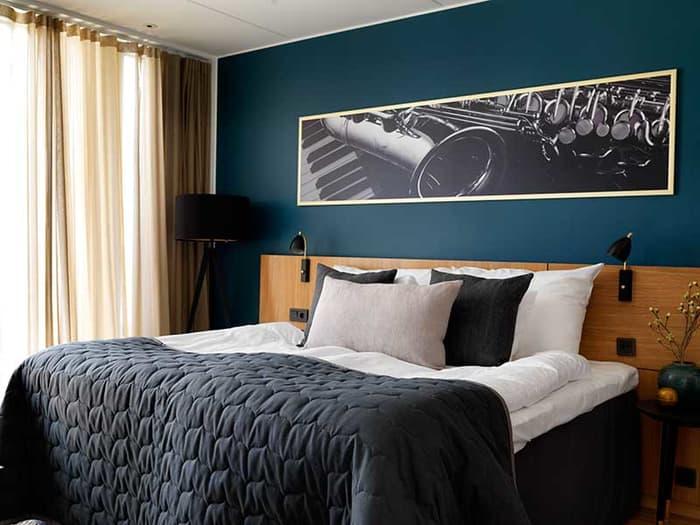 Hotellrom med stor seng og mørkegrønn vegg med bilde