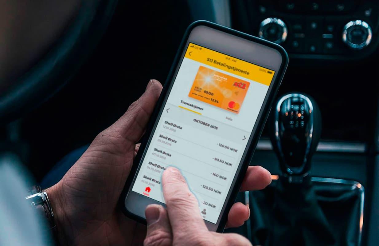 Sjåfør som sitter i bilen oh holder en telefon med bilde av Snarveien-appen
