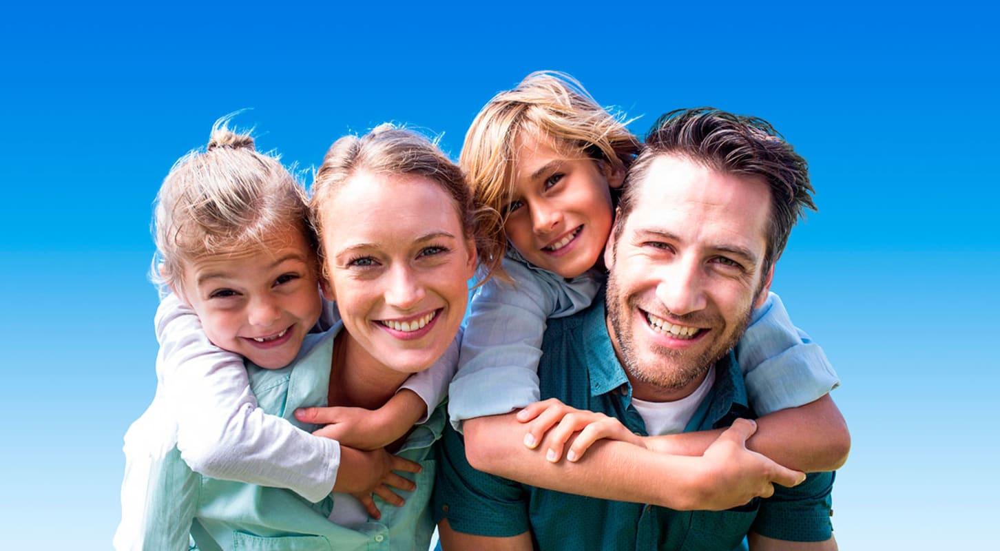 Familie på fire som holder rundt hverandre mot blå bakgrunn