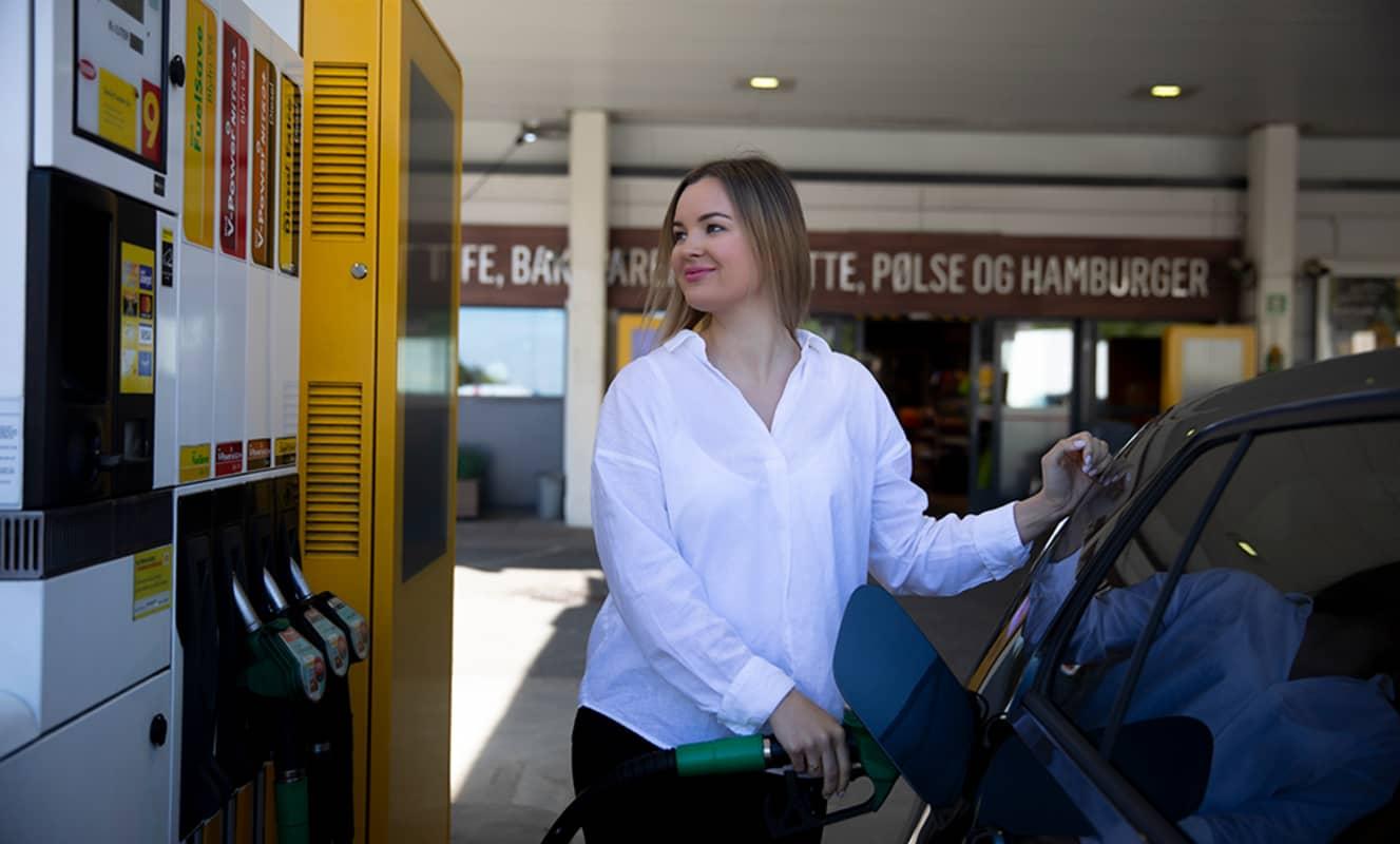 Glad dame som fyller drivstoff på bilen sin hos Shell