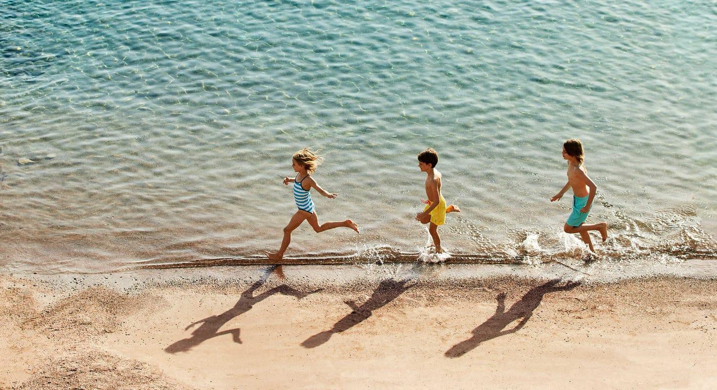 Tre små barn som løper langs stranden i strålende sol og krystallklart vann