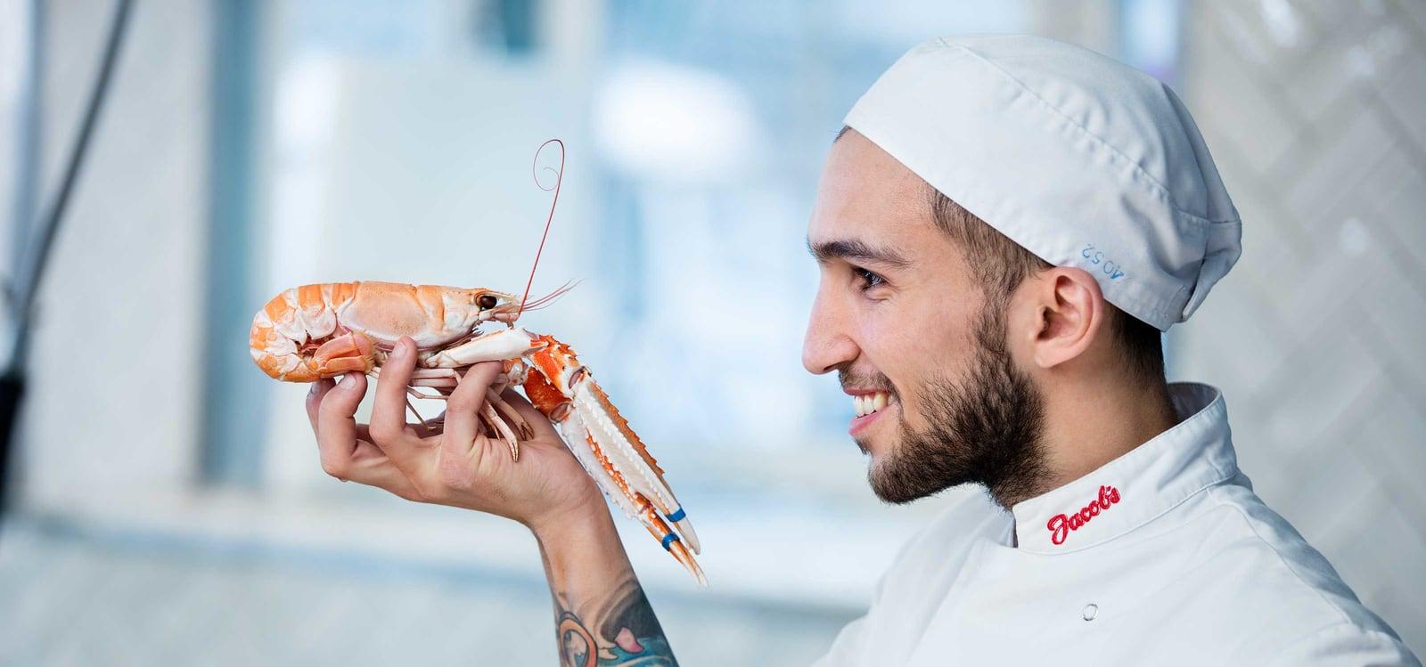 Kokk som holder en hummer mens han ser på den