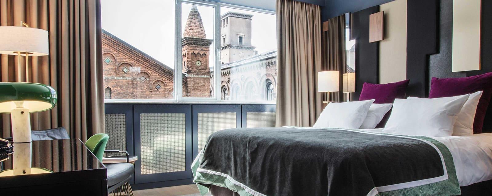 Hotellrom med stor seng og utsikt mot en staselig kirke
