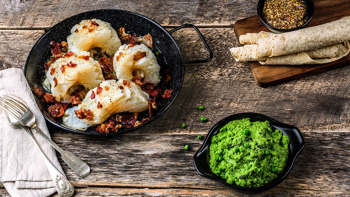 Tradisjonell lutefisk servert med godt tilbehør som ertestuing, bacon, sennepsaus og gode poteter.