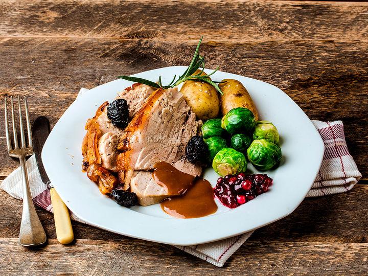 Skinkestek serveres ofte med tilbehør som rosenkål, mandelpoteter og brun saus.