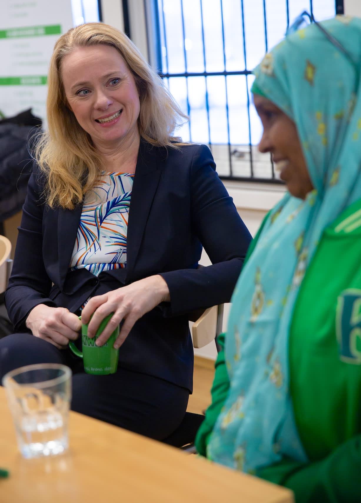 Arbeids- og sosialminister Anniken Hauglie i samtale med Kahadija Mahmed om jakkemerkene.