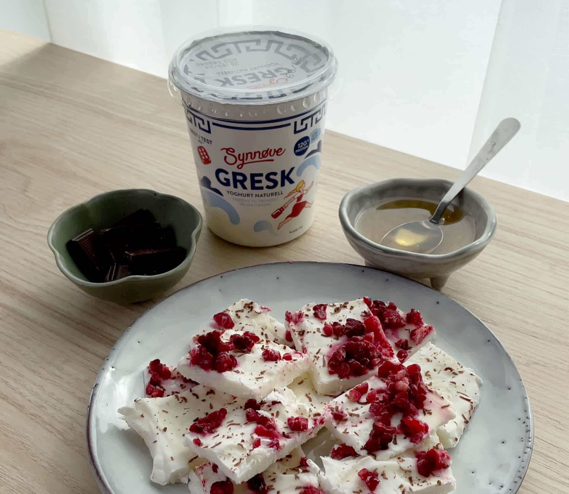 Sunnere snacks med yoghurt toppet med bringebær, mørk sjokolade og honning