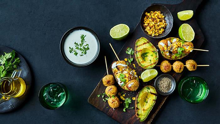 Grillede halve avokado med Veggie Sticks falafel, toppet med yoghurtsaus med hvitløk & mynte og ristet løk & chili crunch