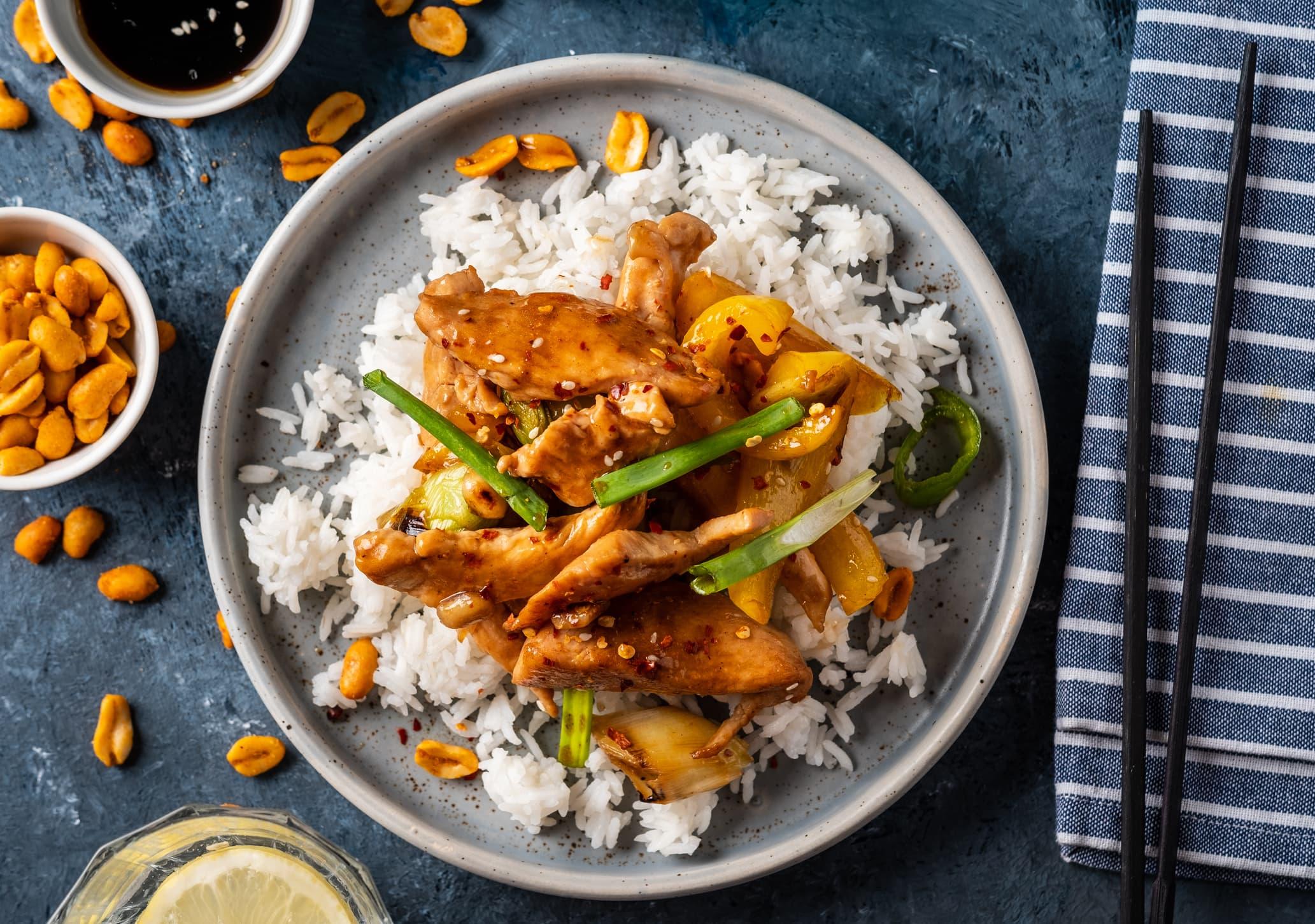 Kyllingrrett servert på ris med peanøtter som tilbehør