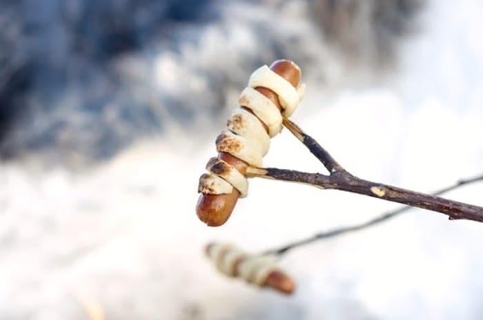 Rull pinnebrød rundt pølsen ogtre den på selvspikket grillpinne.Enkelt, godt og perfekt til barna.