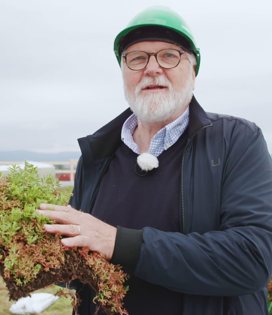 KIWI-gründer, Tor Kirkeng, viser frem gresset som kommer på taket av KIWI Lerberg.