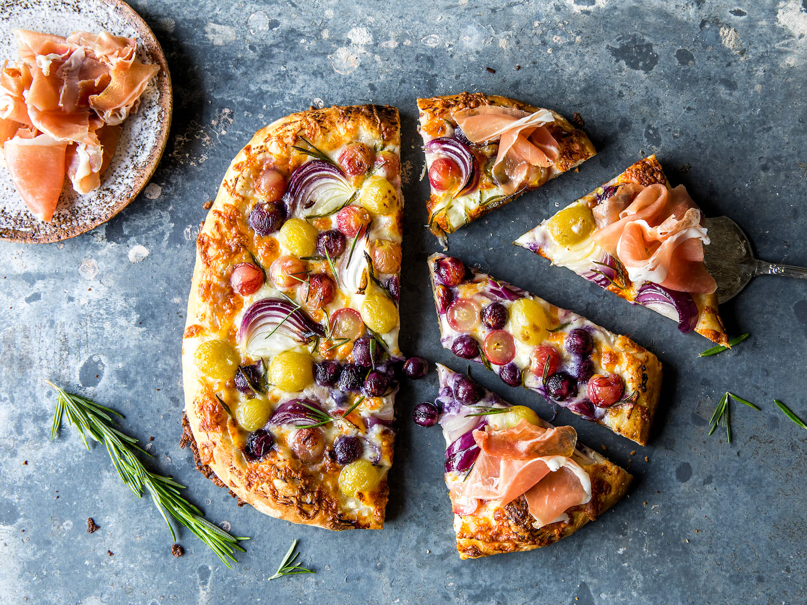 Hvit pizza med druer og spekeskinke