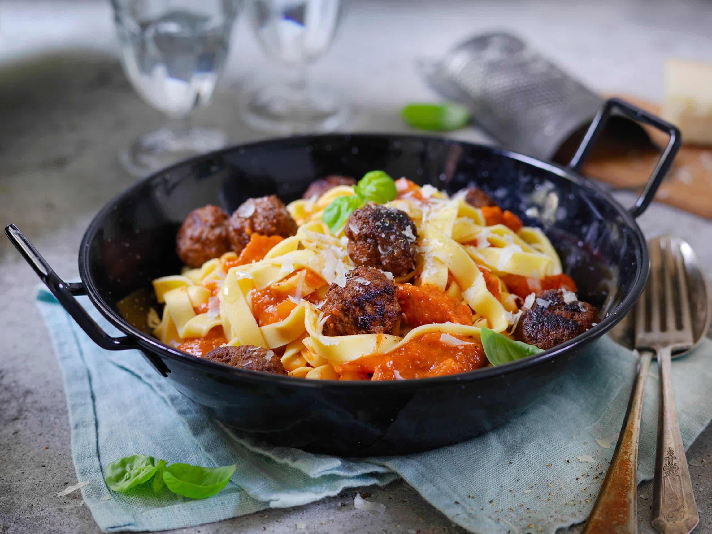 Litt basilikum og parmesan på toppen hever smaken på denne middagen med pasta og kjøttboller i tomatsaus.