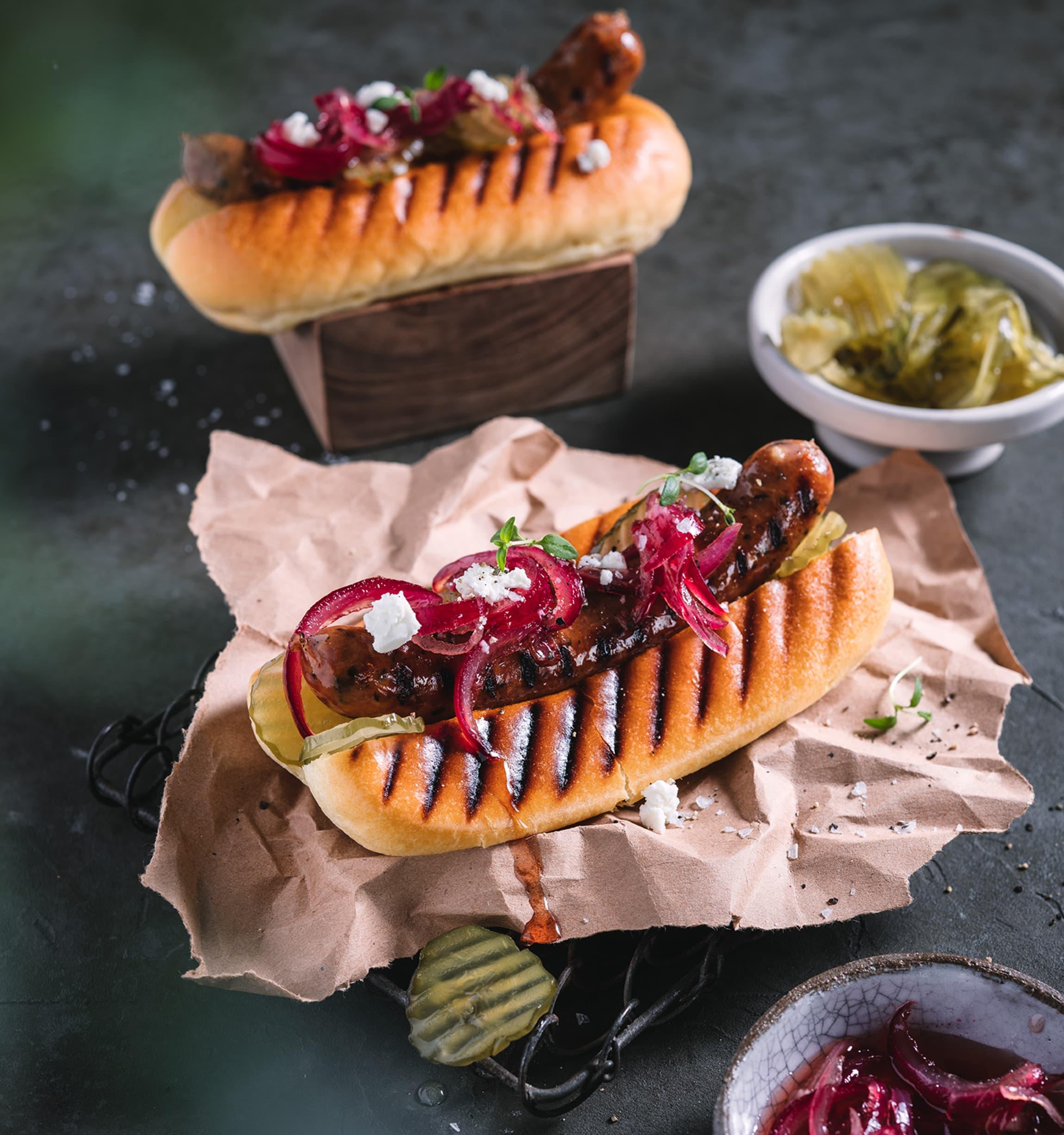 Gourmetpølser med syltet rødløk imponerer grillgjestene i sommer.