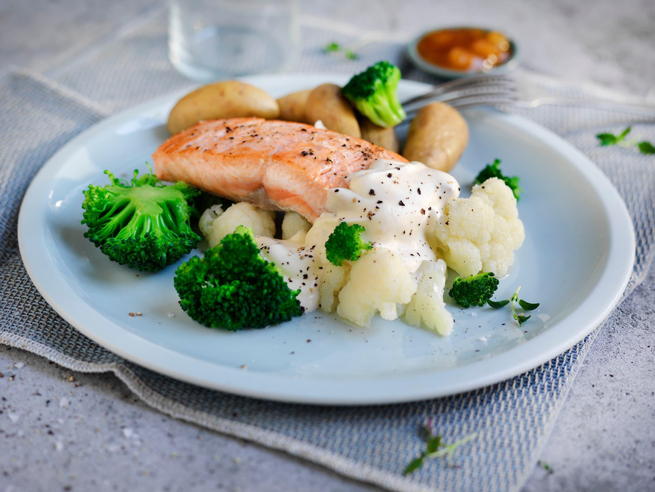 Server en tallerken med stekt laksefilet, poteter og mye grønnsaker. God og sunn middag!