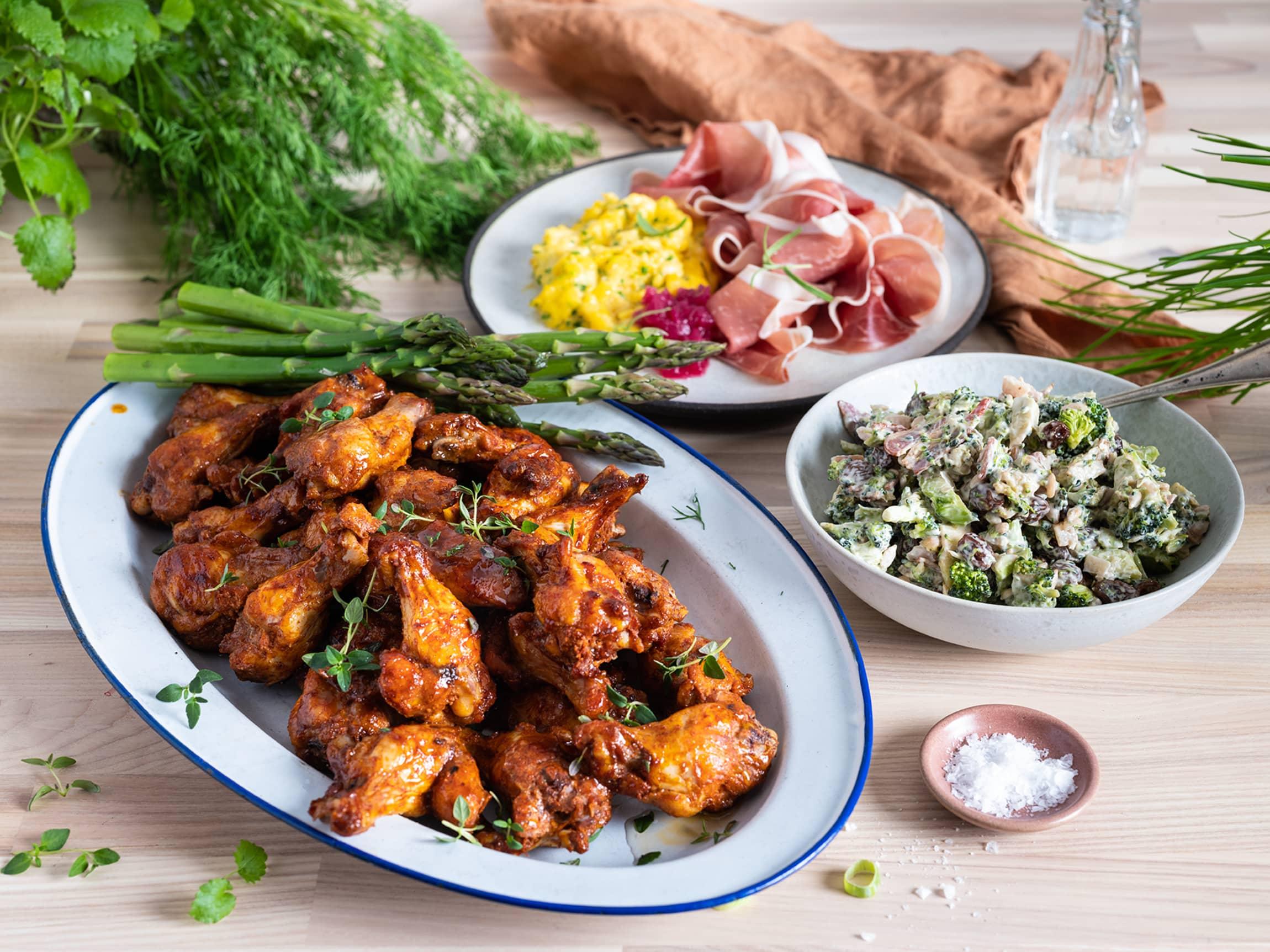Sett frem saftige kyllingklubber, brokkolisalat med bacon, eggerøre og spekeskinke.