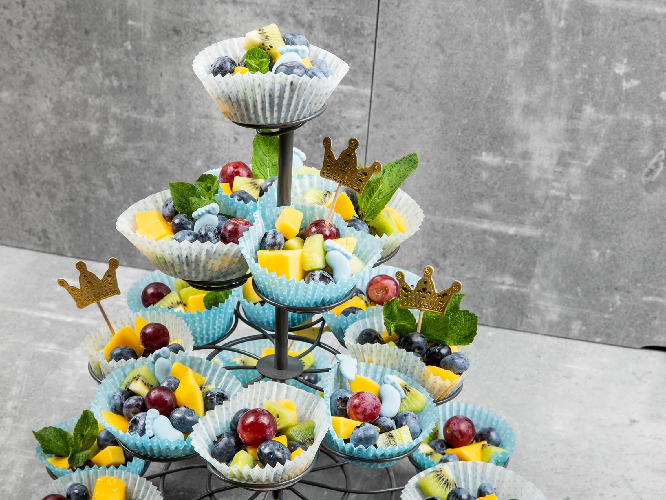 Blå eller rosa muffinsformer fylt med deilig frukt og bær