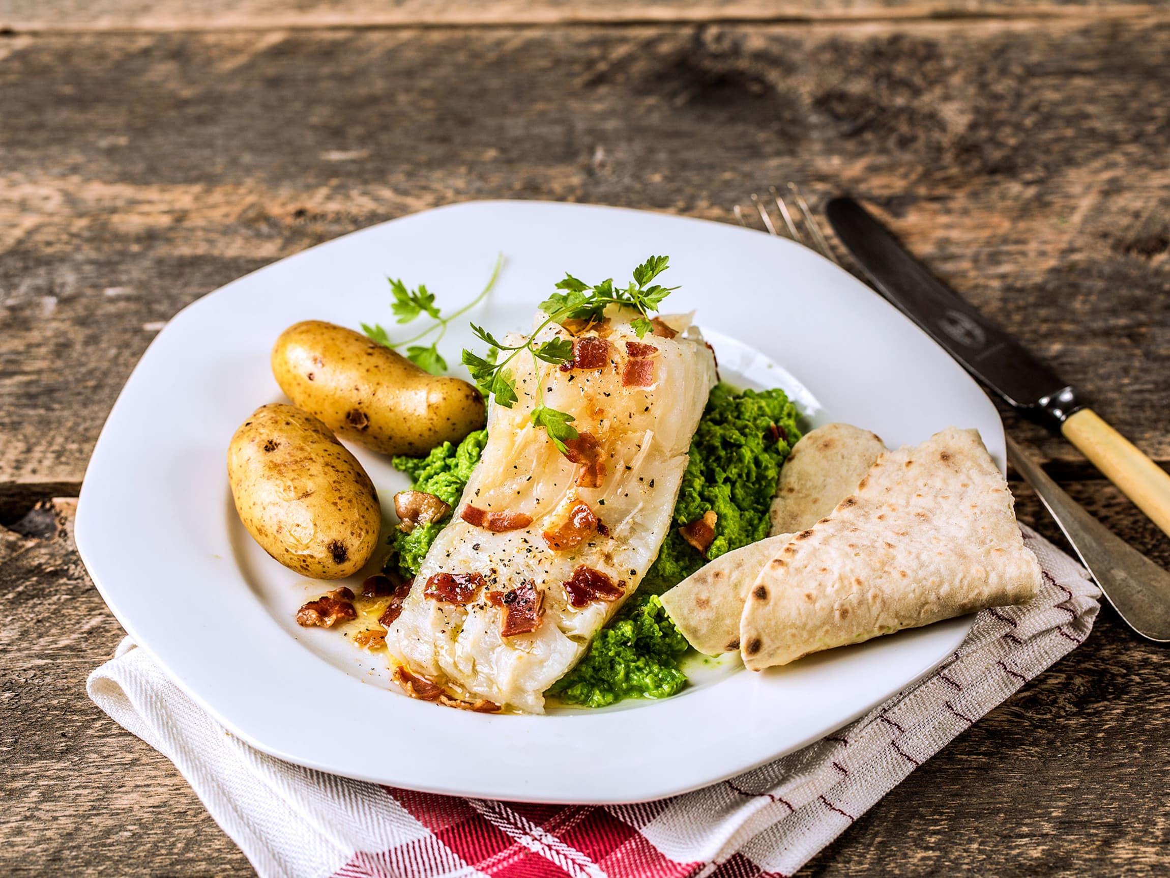 Server lutefisk med tradisjonelt tilbehør som  sprøstekt bacon og nykokte poteter.