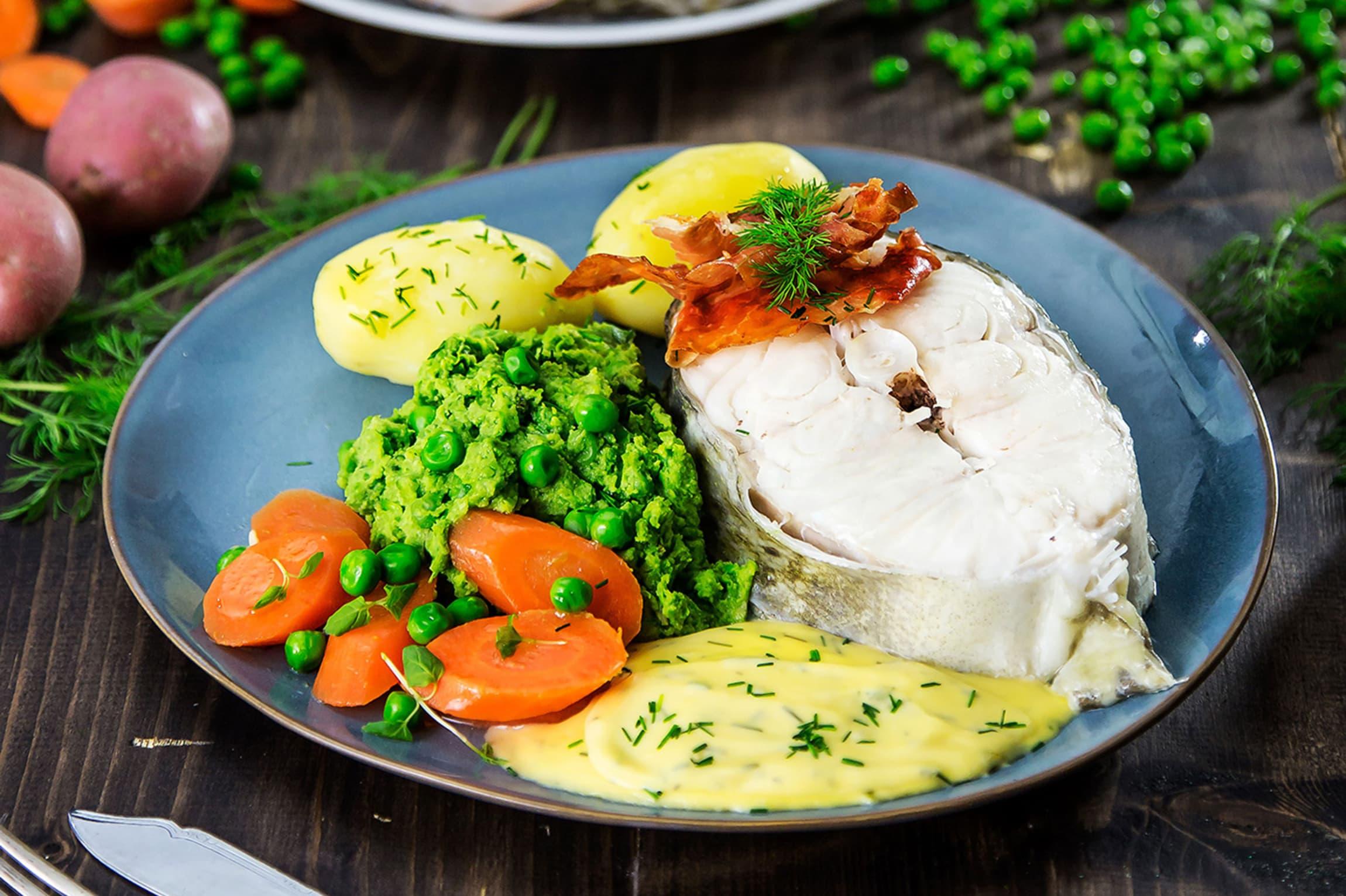 Dette er en tradisjonell måte å servere skrei på, hvor fisken trekkes og serveres med klassisk hollandaise, ertepuré og gulerøtter.