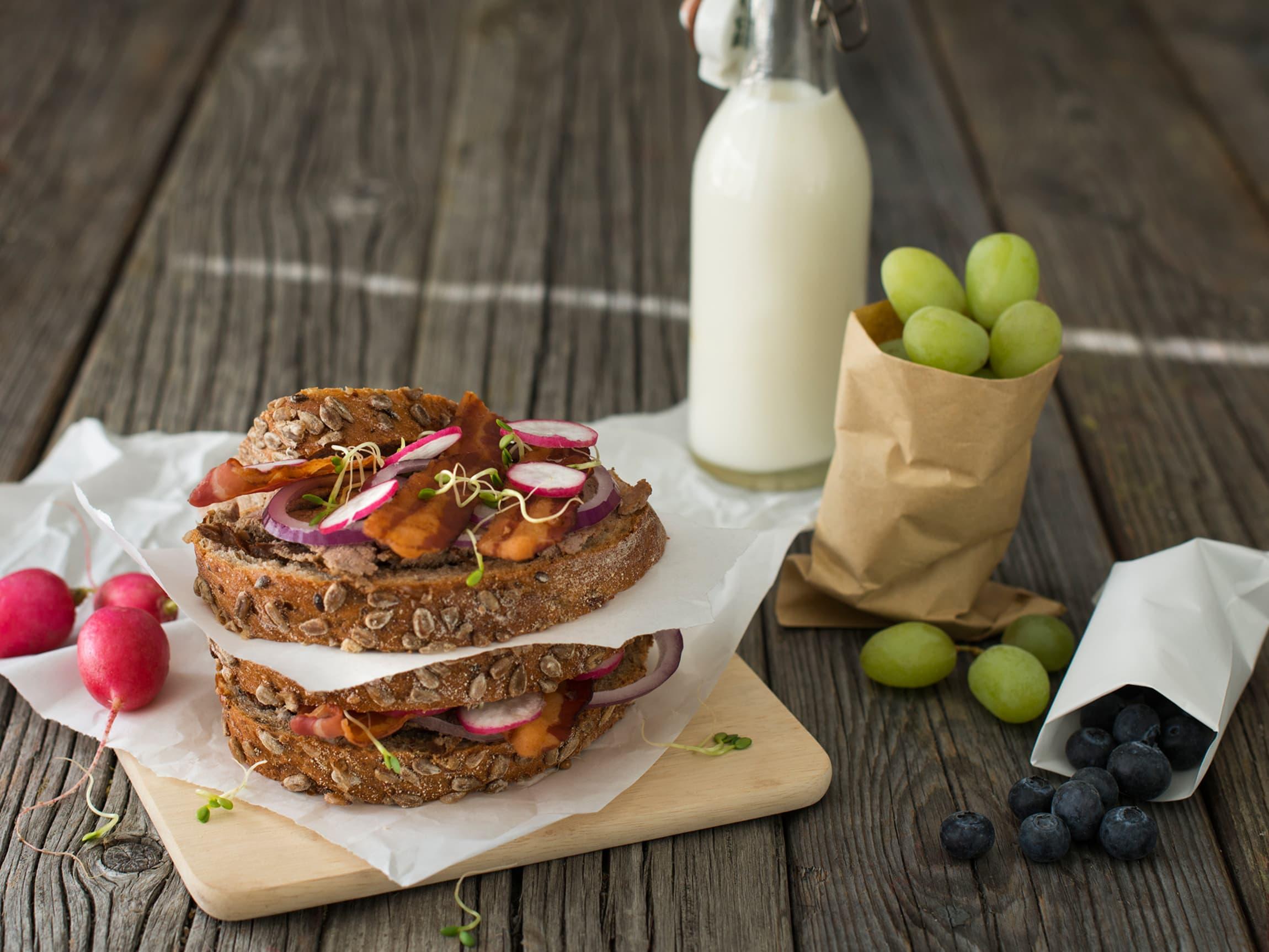 Smør grove brødskiver med leverpostei, toppet med bacon for ekstra god smak.