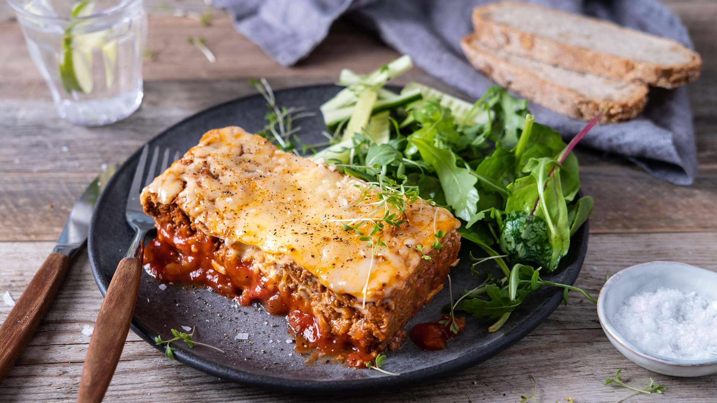 Lag en deilig lasagne med fullkornsplater og server med salat og grovt brød.