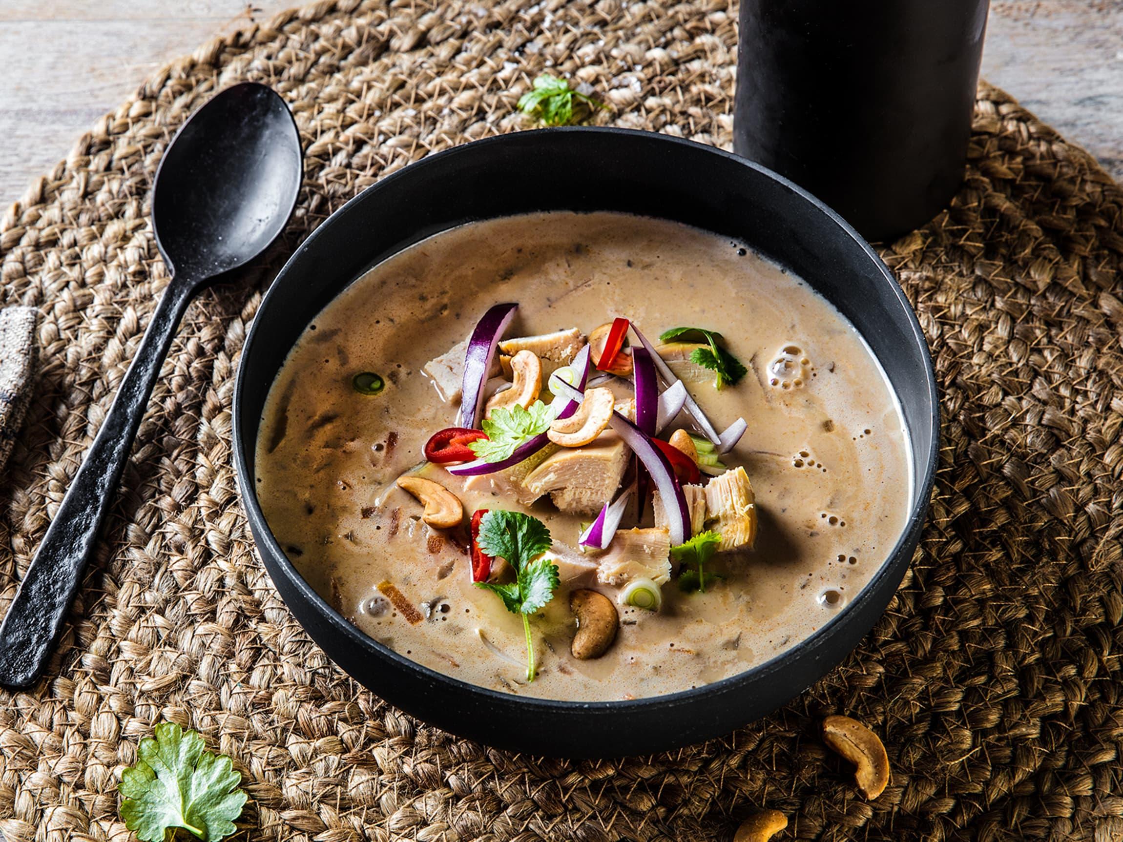 Kremet thaisuppe toppet med kylling, koriander, rødløk og cashewnøtter.