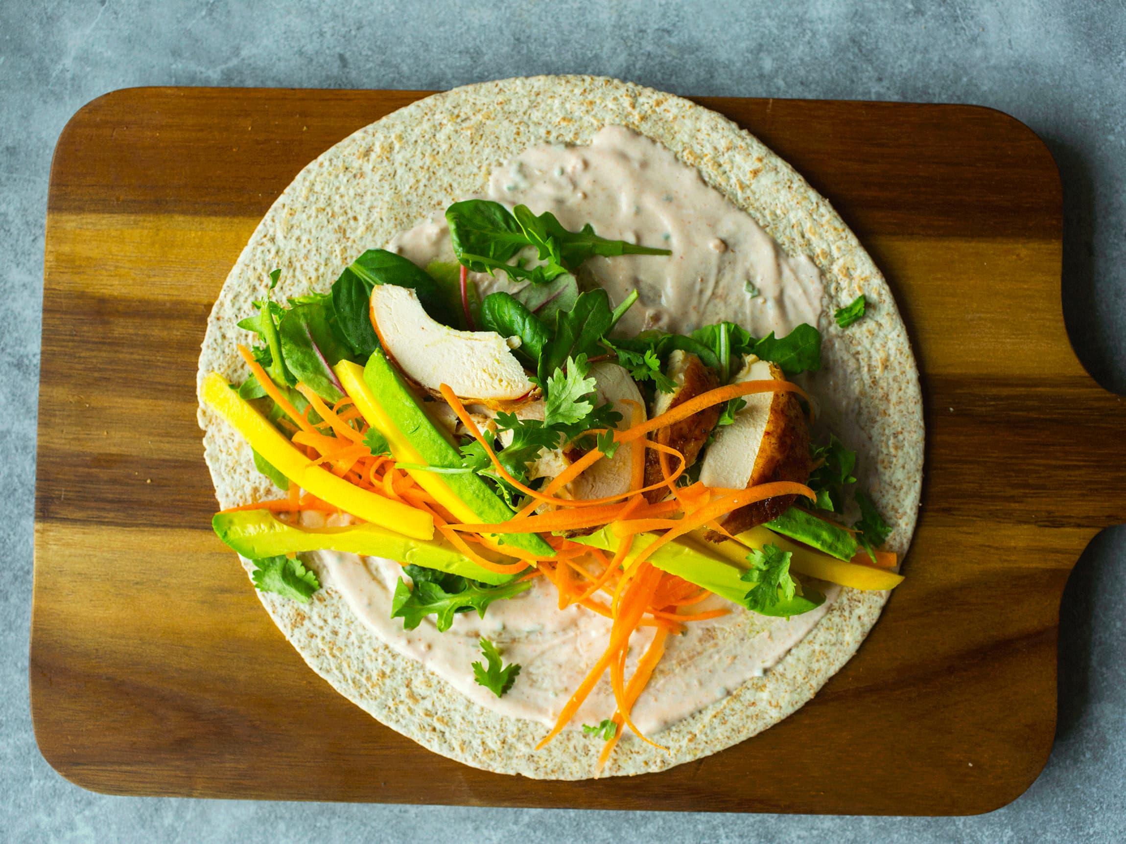 Smør rømme og salsa i grove wraps. Topp med strimlet kylling, mango, avokado og grønnsaker.
