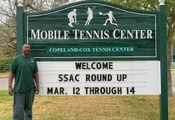 Leonard (Brien) Hawkins, tennis attendant II at Mobile Tennis Center, standing in front of the center's marquee, one of his latest projects. Photo courtesy of Jackie Byerley.