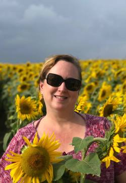Caren Lewis, administrative assistant at Jaffrey Parks and Recreation Department, in a field of sunflowers. Photo courtesy of Renee Sangermano.