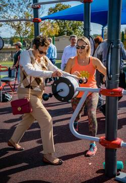 Christie Bruner (left), community engagement supervisor at City of St. Petersburg Parks & Recreation - Healthy St. Pete, helping an AARP board member change the resistance on a hand bike machine. Photo courtesy of Christie Bruner.