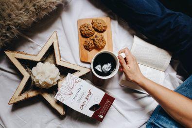 Café et cookie sur un décor de bougie avec notre recette de granola Choco Boost