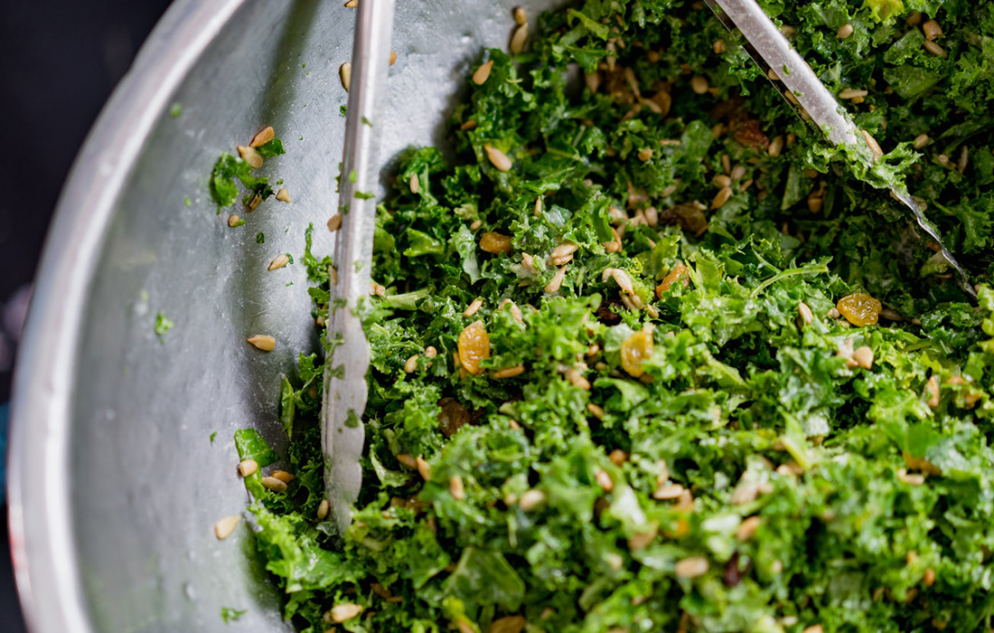 dark leafy super greens in a bowl with tongs