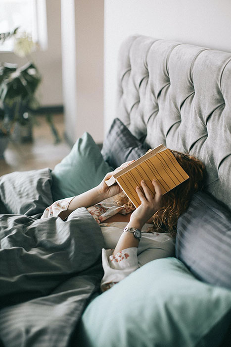 woman lying down with book over her face