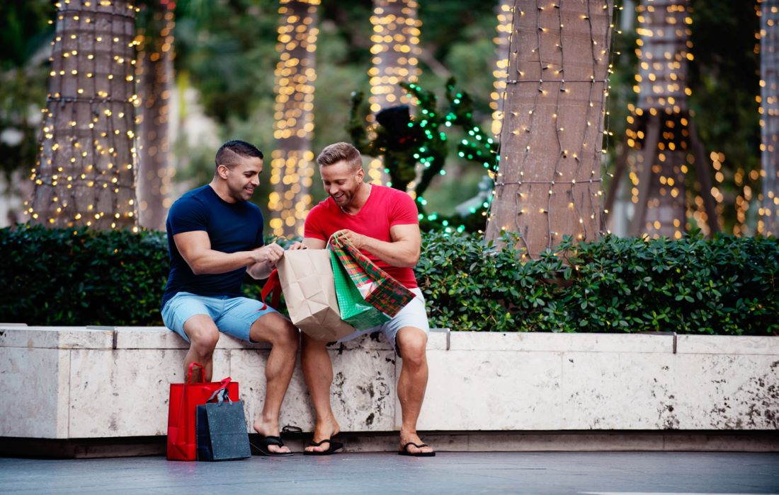 strong men looking at each others christmas shopping bags