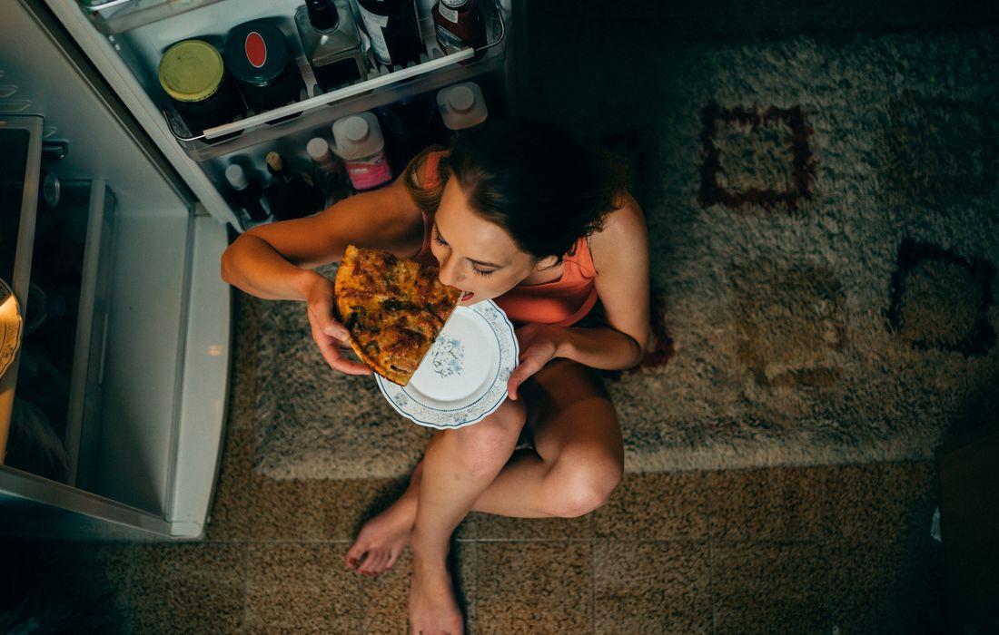 woman eating pizza at night
