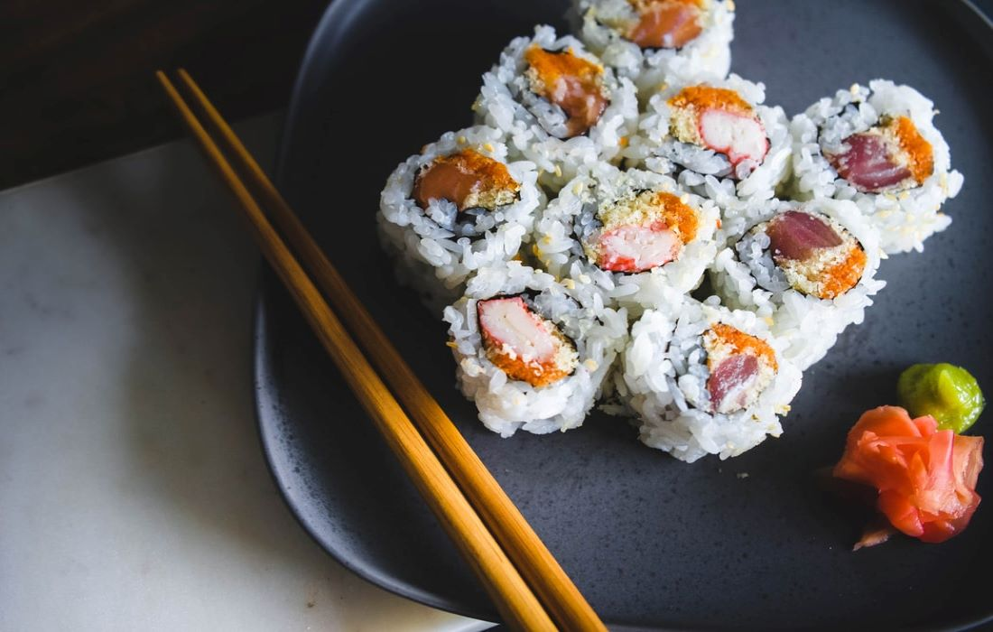 plate of sushi with chopsticks, ginger and wasabi on the side