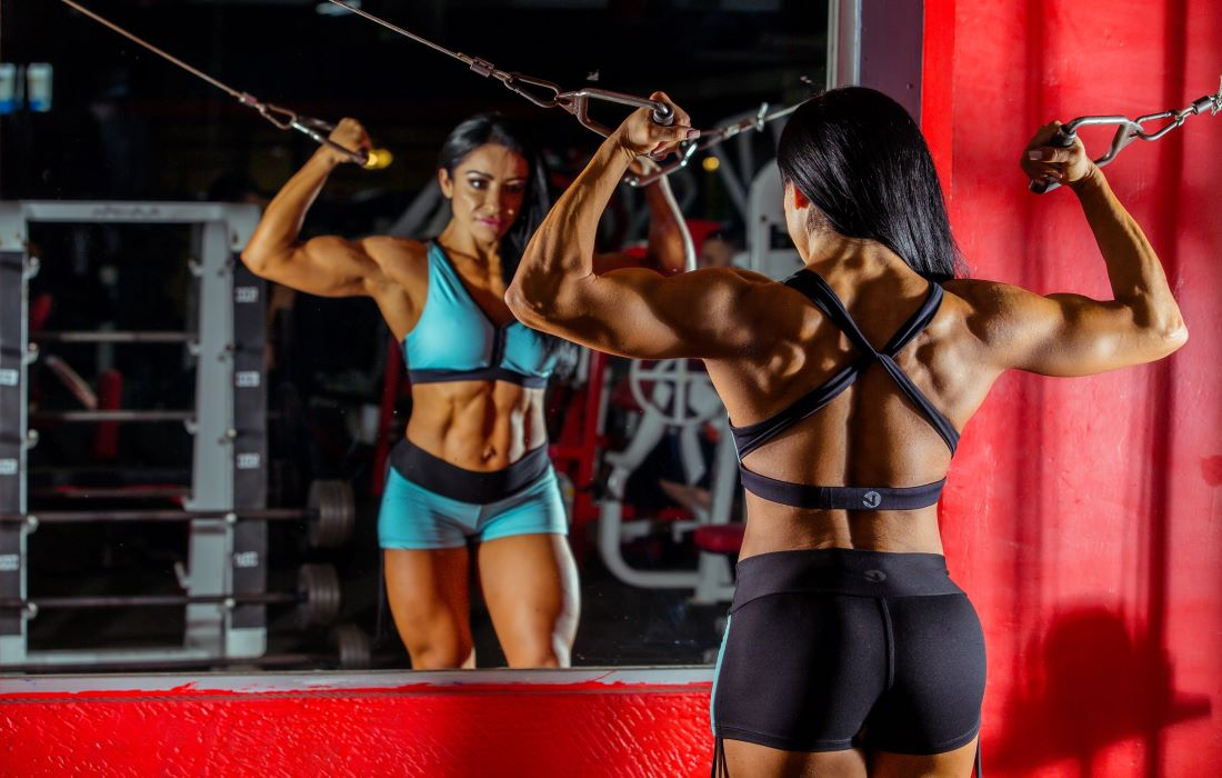 Female bodybuilder doing double bicep curl on cable machine