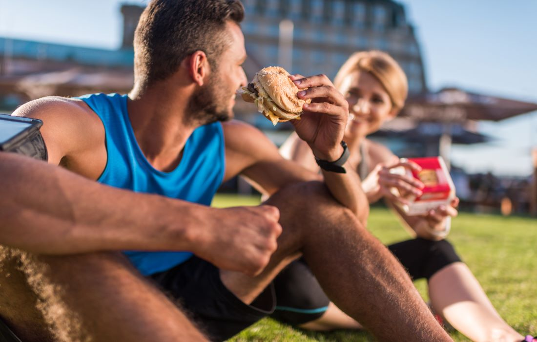 fit couple sitting on grass eating burgers